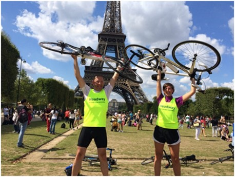 John and Rachel Sandy hold their cycles above their heads in triumph, with the Eiffel Tower behind them on a cloud-speckled but sunny day in Paris
