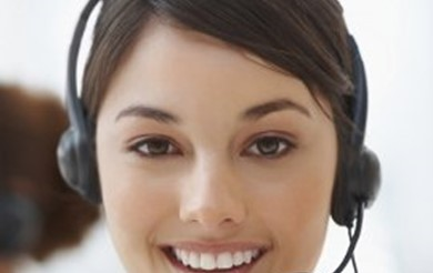 Stock image of a lady smiling at the camera wearing a telephone headset