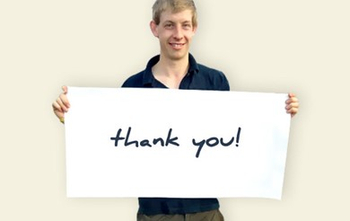 Brain injury survivor Simon Hales holds a sign saying thank you