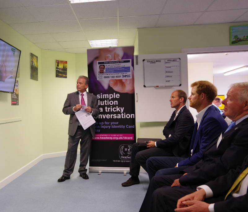 Prince Harry learns about the brain injury identity card in a presentation from Headway Chief Executive, Peter McCabe